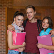 Three smiling students posing in hallway — Stock Photo