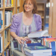 Female mature librarian returning books in library — Stock Photo #36183119