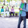 College boy text messaging with blurred students in park — Stock Photo #36183403