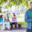 College boy text messaging with blurred students in park — Stock Photo #36183587