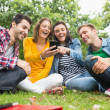 Happy college students looking at mobile phone in park — Stock Photo #36183739