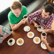 Four smiling students having a cup of coffee chatting — Stock Photo