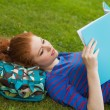 Gorgeous focused student lying on grass reading notes — Stock Photo