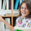Close-up portrait of a smiling female student against bookshelf — Stock Photo