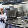 Young happy chef standing next to work surface arms crossed — Stock Photo
