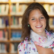 Smiling female student in the library — Stock Photo