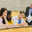 Teacher with students writing notes in lecture hall — Stock Photo