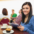 Smiling female having breakfast while using tablet PC at coffee — Stock Photo #36184275