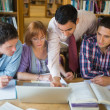Mature students with teacher and laptop in library — Stock Photo #36184279