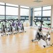 Spinning exercise bikes in gym room — Stock Photo #36184397