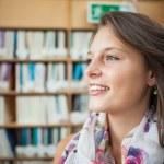Smiling female student against bookshelf in library — Stock Photo