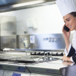 Young smiling chef standing next to work surface phoning — Stock Photo #36184509