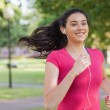 Foto Stock: Sporty pretty woman jogging in a park