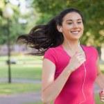 Sporty pretty woman jogging in a park — Stockfoto