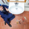 Stock Photo: Cheerful plumber repairing sink showing thumb up
