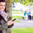 College girl text messaging with blurred students in park — Stock Photo