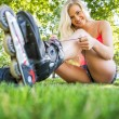 Stock Photo: Casual happy blonde tying shoelaces of roller blades