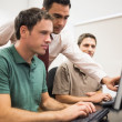 Teacher and mature students in computer room — Stock Photo