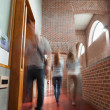 Students walking through hallway away from camera — Stock Photo #36185159