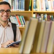 Smiling mature student using tablet PC in library — Stock Photo