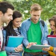 College students with bags and books using tablet PC in park — Stock Photo