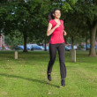 Beautiful woman running in a park — Stock Photo