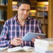 Stock Photo: Mature student using tablet PC in the library