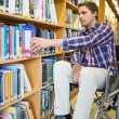 Stock Photo: Disabled wheelchair selecting book in library