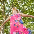 Cheerful blonde woman standing on a lawn — ストック写真