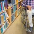 Stock Photo: Low section of a man in wheelchair in the library