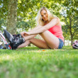 Casual smiling blonde putting on roller blades — Stock Photo