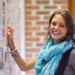Cheerful student touching notice board — Stock Photo #36186337