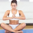 Meditating young woman sitting in lotus position — Stock Photo