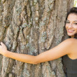 Stock Photo: Casual beautiful brunette embracing tree looking at camera