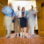 Group of blurred people walking through open doors — Stock Photo #36186821