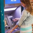 Pretty happy student withdrawing cash — Stockfoto
