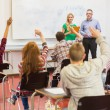 Students raising hands in the classroom — Stock Photo #36187149