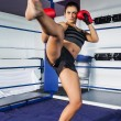 Female boxer performing an air kick in the ring — Stock Photo