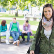College girl smiling with blurred students in park — Stock Photo #36187375