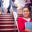 Female holding books with students on stairs in college — Stock Photo #36187777