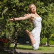 Side view of young fit woman jumping spreading her arms — Stockfoto