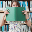 Female student holding book in front of her face in library — Stock Photo #36187875