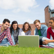 Students using laptop in lawn against college building — Stock Photo