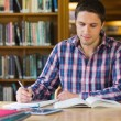 Male student writing notes at desk in the library — Stock Photo #36188087
