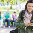 College girl text messaging with blurred students in park — Stock Photo #36188165