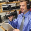 Stock Photo: Well dressed happy radio host moderating