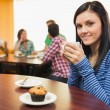 Smiling female having coffee and muffin at coffee shop — Stock Photo