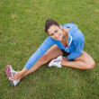 Pretty sporty woman stretching her leg while sitting on the gras — Stock Photo