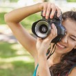 Cute brunette woman taking a picture with her camera — Stock Photo