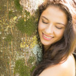 Stock Photo: Casual smiling brunette embracing tree with closed eyes